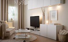 Un salón con armarios de pared, un mueble para TV y armarios, todo en blanco: