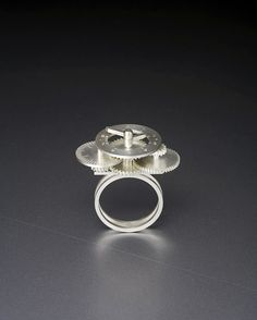 Dukno Yoon, from the Wheels series, These kinetic rings are designed and fabricated with precisely calculated gears and wheels. When the wearer rolls the primary wheel along a surface it measures length, which then can be read by the two hands on the top dial. Similar to the movement of a clock, the shorter hand indicates ten centimeters, the longer hand is used for one centimeter, while the tick marks on the wheel allow the length to also be measured in millimeters.These are kinetic rings…