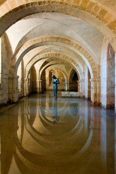 The flooded crypt at Winchester Cathedral, England.This low-vaulted stone crypt, which floods in rainy months, dates from the 11th century, the earliest phase of building the Cathedral, shown here with Antony Gormley's life-size sculpture of a solitary man, Sound II, seen from a distance, between the massive vaults and their reflections. Photo by John Crook