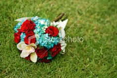 Vibrant flower bouquet red roses orchid blue green grass colorful Royalty Free Stock Photo
