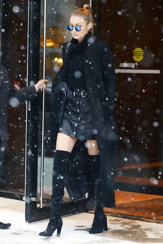 Gigi Hadid wears a miniskirt, sweater, coat, and thigh-high boots in the snow.