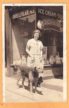 "Photo Postcard of Woman Standing w/Airedale in front of retail pharmacy ""Louis L. Filar, PhG"" c. 1920-30's"