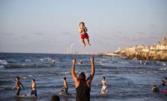 Un hombre juega con su hijo en la playa en la ciudad palestina de Gaza.  MAHMUD HAMS (AFP)