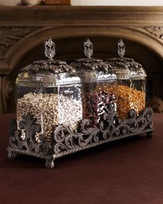GG Collection Three Glass Canisters. 3 textured glass canisters topped by elaborately detailed metal lids and stand.