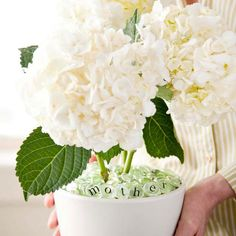 """Simple Mother's Day Flowerpot.......Liven up an ordinary pot of flowers for Mom with customized glass planter fillers. Fill a white ceramic pot with the glass pebbles, adding sticker letters to spell """"Mother"""" to six of the pebbles. Arrange the letter pebbles at the front of the flower pot, then insert a few faux hydrangea stems to finish."""