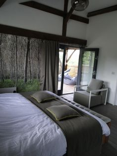 master bedroom with boxx chair leading onto balcony