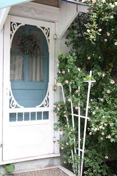 Love love love the gingerbread screen door framing the blue door.