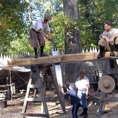 FORT: A young visitor helps the interpreters saw lumber.