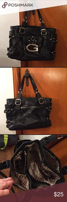 ⭐️HUGE! Black faux leather guess shoulder bag!⭐️ A huge Guess shoulder bag with so many pockets you could lose stuff!!!! Aprox 16 inches across,  9.5 in tall and 8 inches across the bottom. 1 outside zipper pocket. One magnetic closure pocket.  2 side pouches that can each carry a water bottle.  On the inside there are two small magnetic closure pouches on the top, and 2 zipper pouches on the inside.  Please see a picture of the inside. Huge zipper pouch in the middle divides the purse…