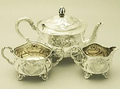 A fine and impressive antique Edwardian English sterling silver three piece bachelor tea service/set in the Art Nouveau style; an addition t...