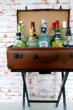 Project Apartment: DIY Faux Bar Table | The Desi Wonder Woman. Repurposed old suitcase on luggage rack to hold bottles; pull out for parties & events. Upcycle, Recycle, Salvage, diy, thrift, flea, repurpose, refashion! For vintage ideas and goods shop at Estate ReSale & ReDesign, Bonita Springs, FL