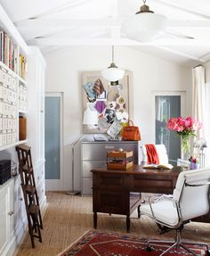 retro white office room with decorative pendant lamps and feminine wooden desk plus red oriental rug