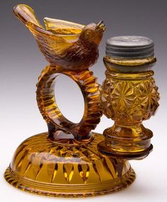 """BIRD FIGURAL COMBINATION SET, amber, stand with center napkin ring surmounted with an open salt, front peg for pepper shaker, along with a similar but inappropriate shaker, period lid. Fourth quarter 19th century. 5 1/4"""" HOA."""