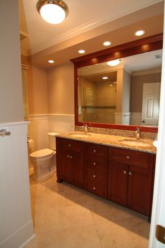 Bathroom Remodel: Jack and Jill sinks; cream colored stone countertops; framed standalone mirror; canister lighting; dark brown wood cabinets