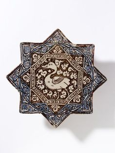 Tile      Place of origin:      Kashan, Iran (probably, made)     Date:      early 14th century (made)     Artist/Maker:      unknown (production)     Materials and Techniques:      Fritware, glazed and painted in cobalt blue and lustre     Museum number:      1508-1876