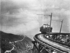 "(1893)^ - Photograph of the first passengers of Professor S.C. Lowe's dramatic Mount Lowe Railway, July 4, 1893. There are a couple of dozen people in the rail car (number ""9"") which is headed toward the camera on the circular bridge. The trestle structure is visible below the rails. The hotel on the mountaintop is visible at left as is the rail approach to the hotel.  (near L.A.)"