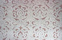 Calista Velvet Fabric An ornately cut velvet fabric with a small circular damask pattern in white on a pink background.