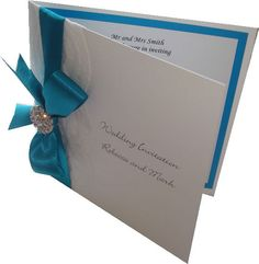 Folded vintage wedding invitation with lace, satin ribbon and a crystal diamante embellishment. Shown in teal blue