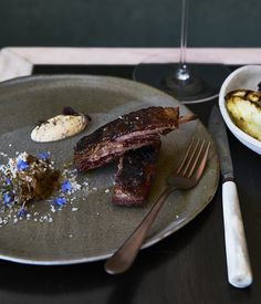 """Curtis Stone shares his recipe the barbecued lamb ribs he plates up at new LA restaurant Gwen. """"Lamb ribs are juicy and delicious to eat right off the bone,"""" says Stone. """"The ribs are covered and cooked low and slow in the oven and are finished uncovered on the barbecue to achieve a good crust."""""""