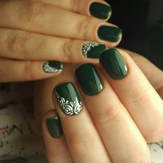 Green and white themed rose nail art design. The nails are painted in dark green polish as the roses on top are drawn in white polish. The contrast works great with both colors as the rose design can be clearly seen.