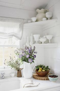 A bowl of lemons, a pitcher of flowers, and white China in a white kitchen