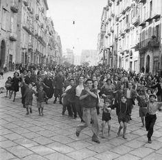 Naples, September - October 1943: A crowd of civilians runs through a street to greet Allied troops arriving in Naples.