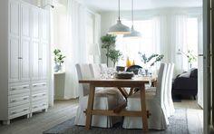 Ljus matplats med ekbord som har plats för åtta personer. Och sex stolar med vita långa stolklädslar.