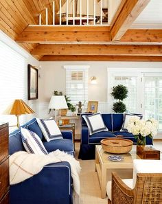 "A summer home on Nantucket Island boasts a classic coastal color scheme. In the living room, knotty pine ceilings warm the crisp navy hues of the sofas and pillows. ""We wanted a casual beach look so we could come in with sand on our shoes or sit on the living room sofa with a wet bathing suit and not worry about it,"" says homeowner and designer Trudy Dujardin."