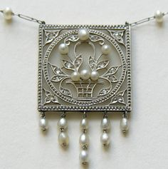 Vintage Frosted Crystal Diamond Pearl 14k Necklace  This elegant necklace is done in the Art Deco style and features a frosted crystal (glass) plaque accented with a white gold flower basket set with diamonds and pearls.   The center part of the necklace measures 1 1/2 inches by 1 inch with the necklace measuring approximately 18 1/2 inches..  The chain is set with pearls and the unusual clasp is marked 14k.  The patent number on the clasp dates this necklace to about 1967.
