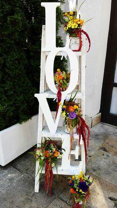 Létrás esküvői dekoráció LOVE felirattal és színes virágdísszel. Vintage esküvőre készítettük az Udvarház Étteremben. | Megtetszett? Neked is szívesen készítünk hasonlót! Kérd ajánlatunkat itt: http://eskuvoidekor.com/spg/887939/Arajanlatkeres