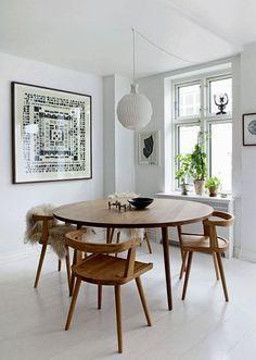 Måltiderne bliver indtaget omkring det runde egetræsbord, som er de designet af Kims eget fifirma, Københavns Møbelsnedkeri. Stolene er også derfra, mens lampen er fra Le Klint. Det grafiske print er Mettes værk, og lignende kan købes hos Oh So Fine. Lampe fra Le Klint