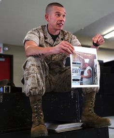 Sgt. Steven Procter, senior drill instructor for Platoon 1034, Alpha Company, 1st Recruit Training Battalion, shows his recruits a photo of himself before he joined the Marine Corps during a guided discussion about commitment on March 18, 2014, on Parris Island, S.C. Procter, a 29-year-old from Lincoln, R.I., shared his story of shedding more than 100 pounds to join the Corps' ranks in hopes that his recruits would be inspired by his dedication.