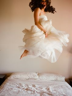 Bride jumping on a bed - feathers added?? Image by Kiss The Groom