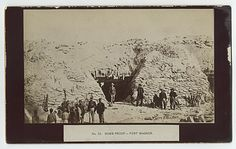 """54th Mass. at Fort Wagner. Mounted albumen 8 1/4 x 5 1/2"""", bearing mounted title: """"No. 33. Bomb-Proof -- Fort Wagner."""" at bottom center. Several Black soldiers in the 54th Massachusetts can be seen in the extreme foreground inspecting the ruins of the recently captured fort. A later photograph taken from the original negative."""