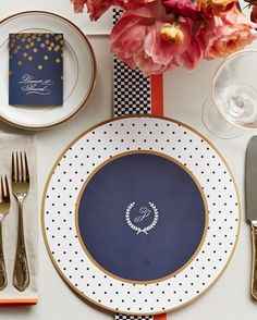 """Lydia and Barritt's wedding monogram, an ornate """"P"""" surrounded by a laurel wreath, elevated the paper chargers at the post-ceremony feast, while alternating lengths of checkered and solid grosgrain ribbons jazzed up the table."""