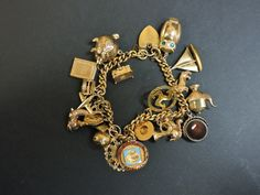 A curb link charm bracelet, with a padlock clasp and safety chain, twenty assorted charms all marked 9ct gold or tested as approximately 9ct gold, one tested as approximately 18ct gold, stamped 750 Sold for £440 on 21st October 2015