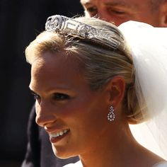 Zara on her wedding day wearing the Meander tiara, which was a wedding gift to Princess Elizabeth from her mother-in-law Princess Andrew of Greece & Denmark (born Princess Alice of Battenberg), Zara's great-grandmother. It is in the classical Greek 'key pattern' & has a large brilliant cut diamond in the centre surrounded by a diamond wreath with a central wreath of leaves & scrolls on either side. The Queen never wore this tiara in public; she passed it on to Princess Anne around 1972.