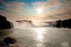 Goðafoss on a sunny afternoon. Tourists stand on the edge of the fall and admire it.