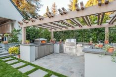 U shaped outdoor kitchen is fitted with stainless steel cabinets and concrete countertops accompanied by an outdoor pizza oven, bbq and outdoor sink shaded by a pergola. Build Outdoor Kitchen, Outdoor Kitchen Countertops, Outdoor Kitchen Design, Outdoor Cooking, Concrete Countertops, Outdoor Kitchens, Patio Kitchen, Concrete Tiles, Modern Outdoor Pizza Ovens