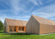 Narrow strips of wood screen both walls and windows at this house in Bavaria by Kühnlein Architektur, which comprises a pair of connected sheds.