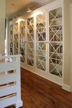 Built-in bookcase wall with glass doors. What makes this even better is the lighting.