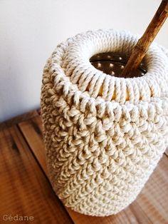 Un pot de confiture grand format, de la cordelette coton, (magasins de bricolage) un anneau de rideau, et un crochet. Crocheter la cordelette autour de l'anneau, puis en mailles serrées sans augmenter, quand on arrive à hauteur voulu on insère le pot,...