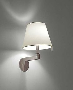 Melampo mini wall sconce by Artemide by Artemide. $375.00. Product Description: The Melampo miniwall sconce from Artemide has been designed by Adrien Gardere. This wall mounted luminaire with adjustable diffuser is perfect for direct and indirect diffused incandescent lighting. The Melampo is constructed of die-cast aluminum with your choice of a grey or bronze powder finish. The diffuser is made from polycarbonate fiber blendwhich is available in grey or beige. Th...
