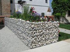 Eine Möglichkeit, Natursteine für ein Hochbeet einzusetzen, ohne zu mauern, sind sogenannte Gabionen. Diese Körbe aus Drahtgitter können mit unterschiedlichsten Steinarten befüllt werden. Wem die eigenhändige Befüllung zu mühsam ist, kann dies auch vom Fachmann erledigen lassen.