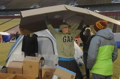 """CJ Pilcher, of United Church of Christ youth group, in Ames, makes a shelter with cardboard boxes during the """"Reggie's Sleepout"""" event at Jack Trice Stadium Saturday, March 25, 2017, in Ames, Iowa. Photo by Nirmalendu Majumdar/Ames Tribune"""
