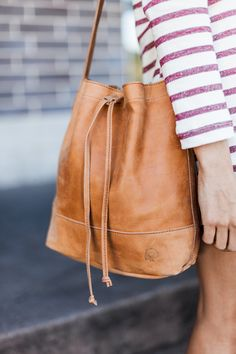 Handcrafted in Ethiopia, the Tadessee bucket bag features minimal detailing, a roomy interior, and soft, slouchy leather.