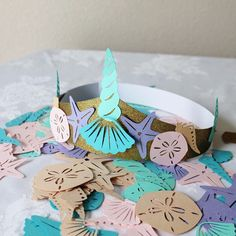 Set of 12 DIY mermaid crown kit. Includes 12 crowns in glitter gold or glitter silver. 150 piece paper shells. 5 colors, two sizes and 5 different kinds of shells or starfish. Crowns are adjustable in size to fit any childs head. Great craft idea at your mermaid party! Everyone gets to be an ocean princess!