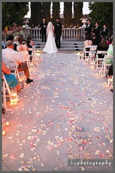 Floating candles and rose petals as aisle borders.