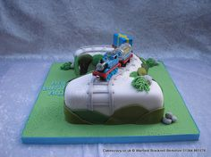No2 Thomas The Tank Engine Cake. Number two numeral shaped birthday cake covered in white with simple country side decoration and topped with a Thomas the tank engine keepsake toy