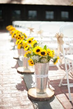 A bright, earthy wedding ceremony aisle. Wood slabs + galvanized buckets + sunflowers